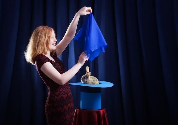 Garota mostra foco com um coelho em um chapéu