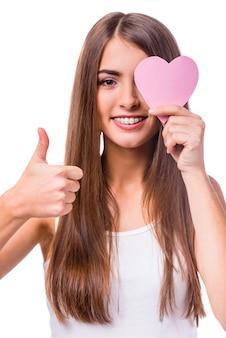 Garota mostra gesto ok e fecha o olho com um coração.