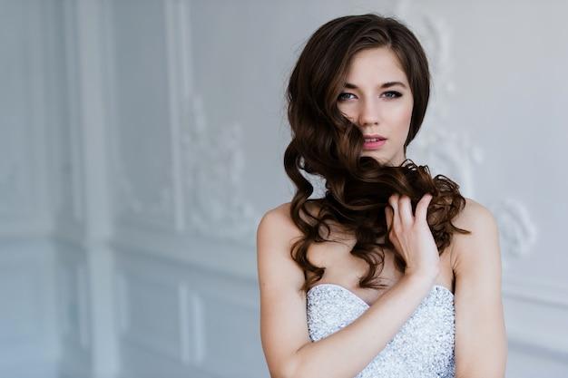 Garota mostra penteado. alegre noiva segurando seus cabelos cacheados.
