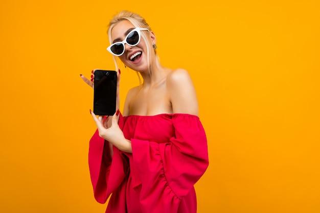 Garota mostra uma tela de telefone em branco com um layout em uma parede laranja