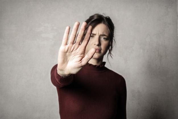 Garota mostrando o gesto de parada