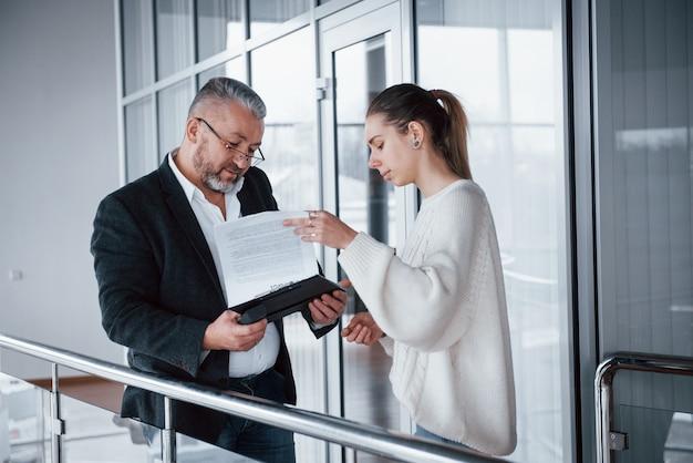 Garota mostrando os resultados do trabalho para o chefe em óculos e barba grisalha