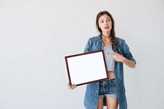 Garota mostrando para um cartaz ou cartaz branco em branco vazio