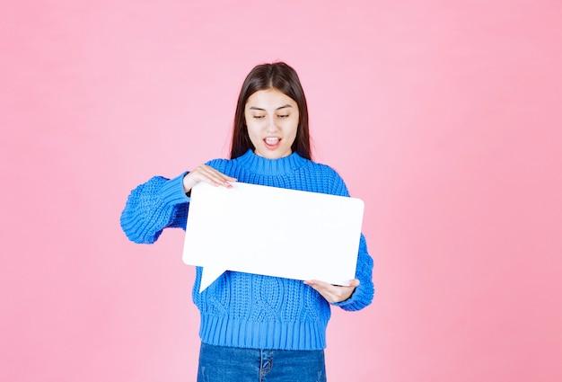 Garota mostrando sinal banner de bolha do discurso e parece feliz em rosa.