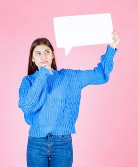 Garota mostrando sinal banner de bolha do discurso em rosa.