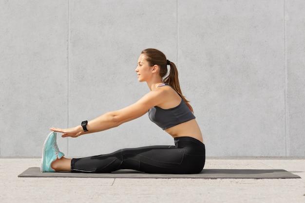 Garota motivada faz exercícios de alongamento ou acrobacias no tapete de fitness, recebe aula de ioga, tem cabelo escuro penteado na cauda de pônei