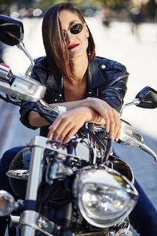 Garota motociclista em uma jaqueta de couro em uma motocicleta