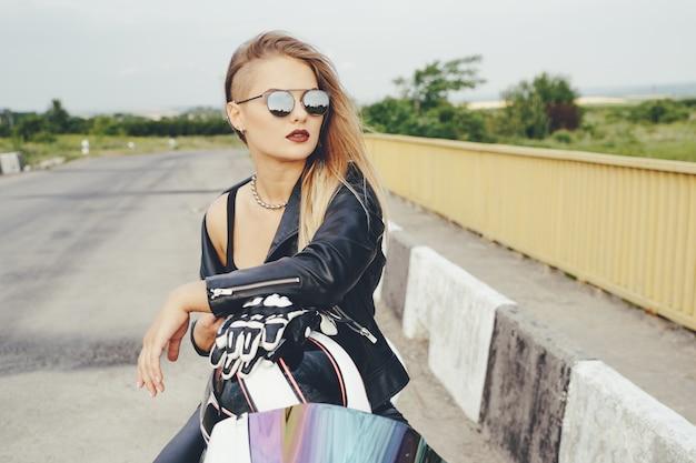 Garota motociclista em uma roupa de couro em uma motocicleta