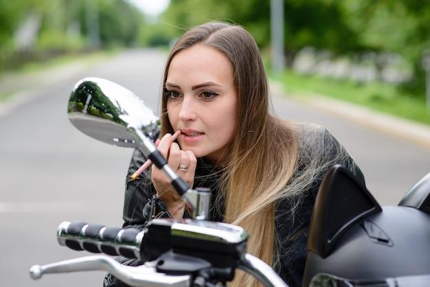 Garota motociclista pinta os lábios em uma motocicleta.