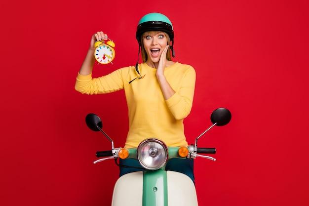 Garota motoqueira louca surpresa dirigindo motocicleta segurando relógio impresso na parede vermelha