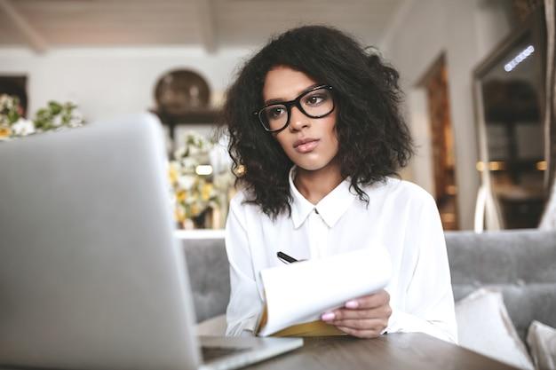 Garota muito afro-americana de óculos, trabalhando no laptop no restaurante. jovem senhora com cabelo escuro encaracolado sentada num café com o caderno na mão