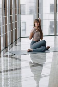 Garota muito atraente fazendo yoga e relaxando na sala iluminada