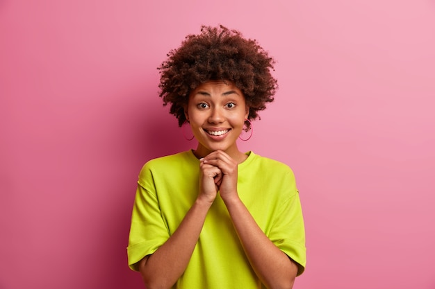 Garota muito bonita com cabelo encaracolado, mantém as mãos sob o queixo, sorri feliz, tem dentes brancos, usa uma camiseta verde casual, posa