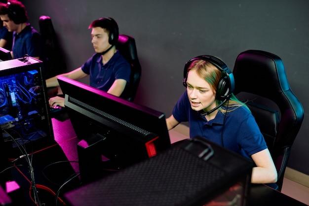 Garota muito cabeluda usando um fone de ouvido falando com alguém enquanto está sentado em frente ao monitor do computador e olhando para a tela durante o videogame