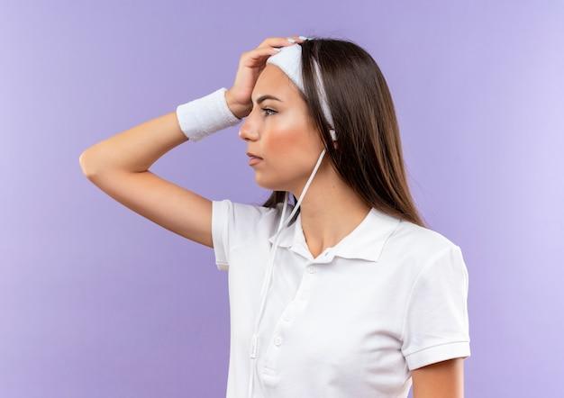 Garota muito esportiva usando bandana, pulseira e fones de ouvido, colocando a mão na cabeça, olhando para o lado isolado no espaço roxo