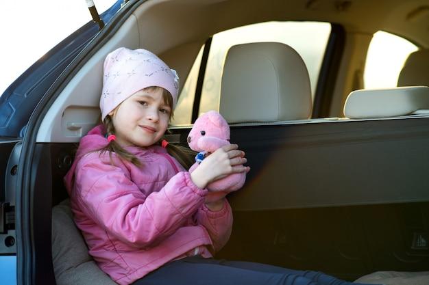 Garota muito feliz criança brincando com um urso de pelúcia rosa brinquedo sentado em uma mala do carro.