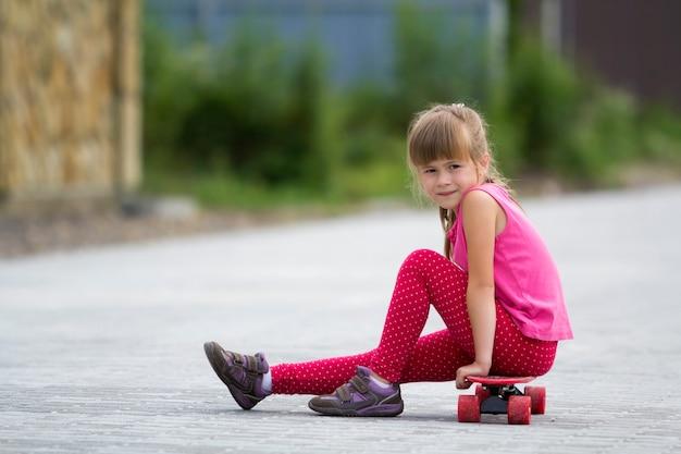 Garota muito jovem criança loira cabelos compridos em roupas casuais-de-rosa, sentado no skate na rua pavimentada do subúrbio