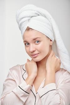 Garota muito limpa com pijama de seda vai cuidar do rosto e do corpo após o banho matinal e lavar o cabelo