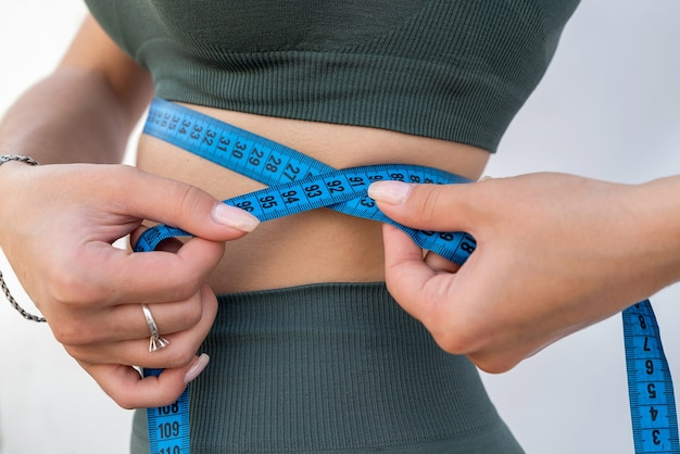 Garota muito magra em roupas esportivas verdes mede sua cintura com uma fita centímetro. conceito de saúde e dieta