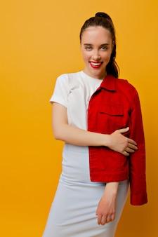 Garota muito moderna vestida de jaqueta vermelha, camiseta branca e saia azul com lábios vermelhos e cabelo recolhido posando com sorriso e parece feliz, emoções verdadeiras, garota estilosa, moda
