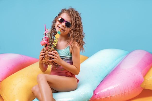 Garota muito sorridente com cabelos cacheados, vestindo roupas de banho rosa e azul, óculos escuros e segurando o cocktail de abacaxi