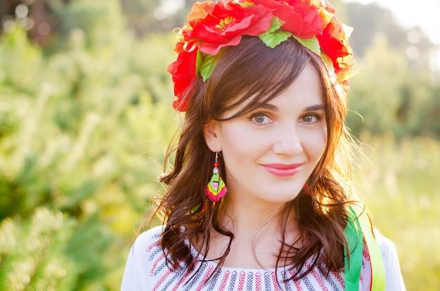 Garota muito sorridente em uma guirlanda de flores de papoula e vestido étnico bordado nacional, posando em pequenos pinheiros, iluminados com raios de luz do sol