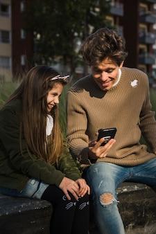 Garota muito sorridente, sentado no parque com o pai dela, segurando o telefone celular