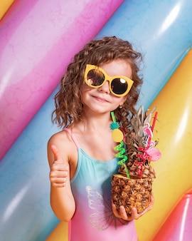 Garota muito sorridente, vestindo roupas de banho-de-rosa e azuis e óculos de sol segurando abacaxi cocktail com canudos coloridos
