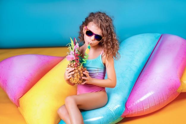Garota muito sorridente, vestindo roupas de banho-de-rosa e azuis e óculos escuros, segurando o abacaxi cocktail com canudos coloridos e aparecendo o polegar no colchão inflável de arco-íris