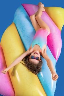 Garota muito sorridente, vestindo roupas de banho rosa e azul e óculos de sol levantou as mãos enquanto está deitado, relaxe no colchão inflável de arco-íris