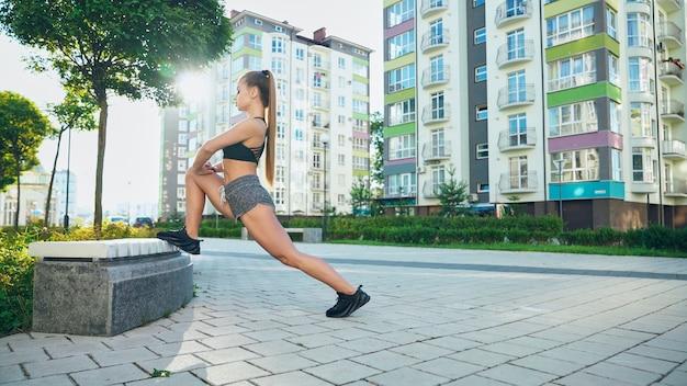 Garota muscular e flexível esticando a perna no banco ao ar livre.