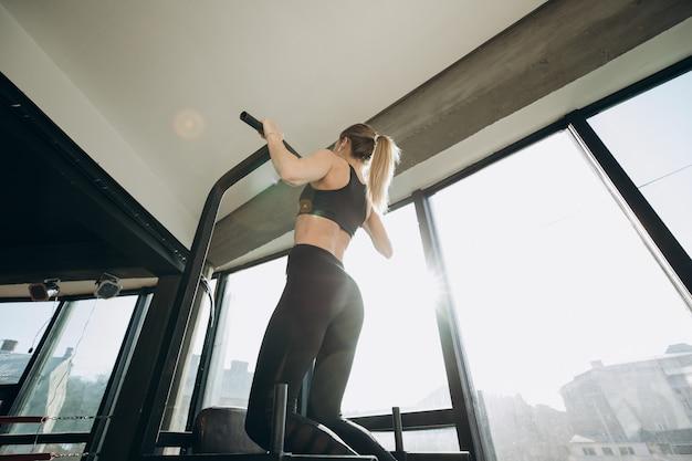 Garota musculosa, atlética, fisiculturista, em shorts curtos, puxada em um simulador de esportes