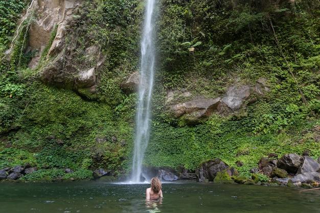 Garota na cachoeira de lagoa de água doce azul remota nas selvas. sudeste asiático