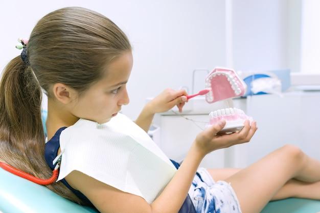 Garota na cadeira odontológica, com escova de dente