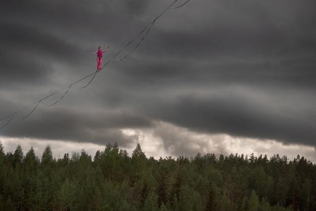 Garota na corda bamba caminhando ao longo da linha alta sobre a floresta
