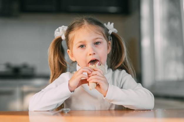 Garota na cozinha tomando sorvete, luz do dia, pôr do sol muito doce