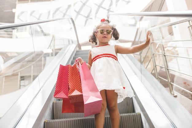 Garota na escada rolante do shopping com compras