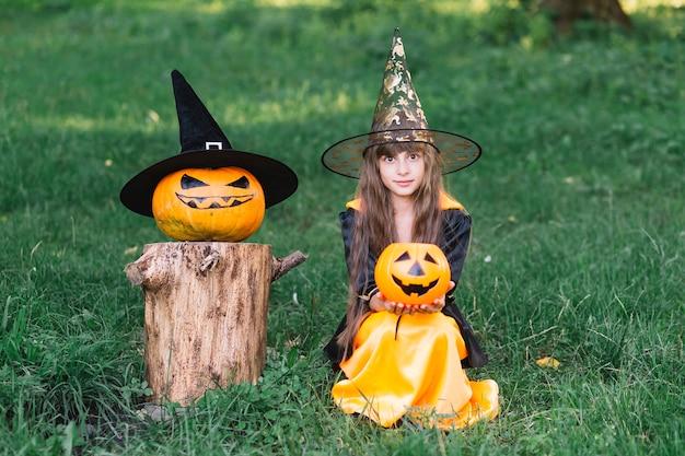 Garota na fantasia de bruxa, sentado na grama perto de abóbora