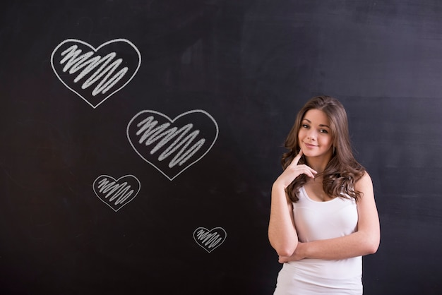 Garota na frente do quadro negro está pensando em se apaixonar.