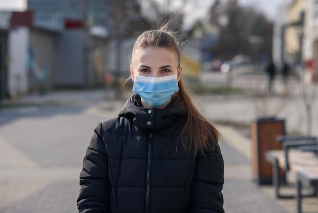 Garota na máscara protetora e luvas usando smartphone ao ar livre. covid 19. pandemia mundial de coronavírus.