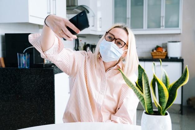 Garota na máscara protetora, sentado em casa e segurando a videochamada.