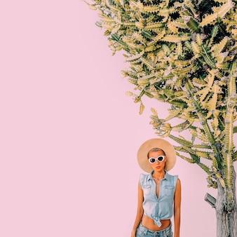 Garota na moda, acessórios de verão e roupa jeans em local cactos viaje com clima tropical