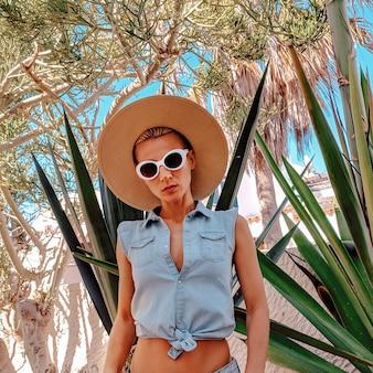 Garota na moda - acessórios de verão em um local tropical - clima de moda para viagens