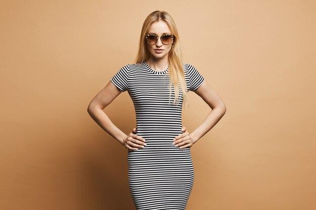 Garota na moda e bela modelo loiro com corpo esbelto e elegantes óculos de sol de oncinha, posando de vestido listrado preto e branco glamourosa