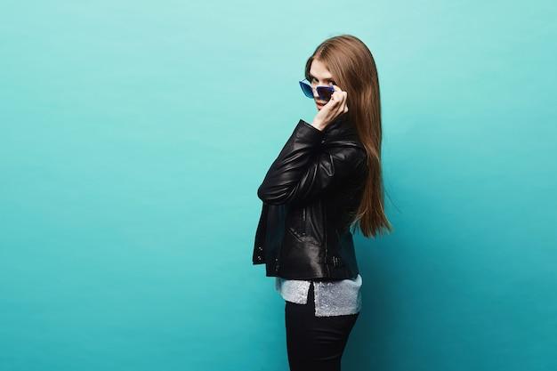 Garota na moda modelo loira com corpo perfeito na jaqueta de couro preta e óculos elegantes posando no azul