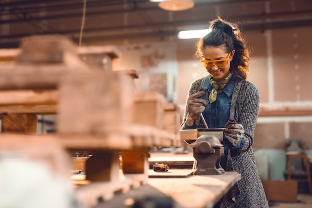 Garota na oficina de carpintaria, fazendo o trabalho de madeira com óculos de proteção.