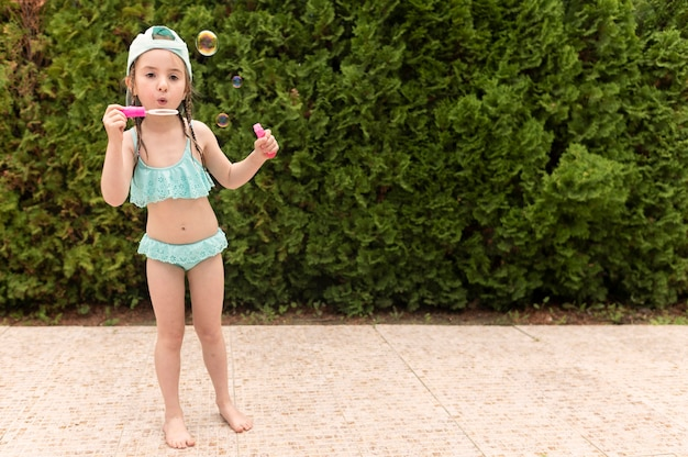 Garota na piscina fazendo bolhas de sabão