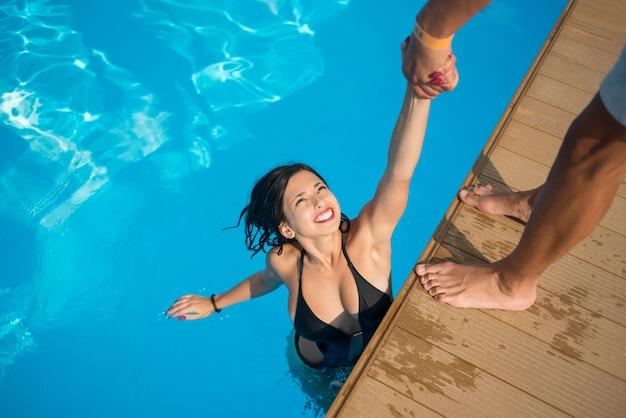 Garota na piscina segurando a mão de um homem