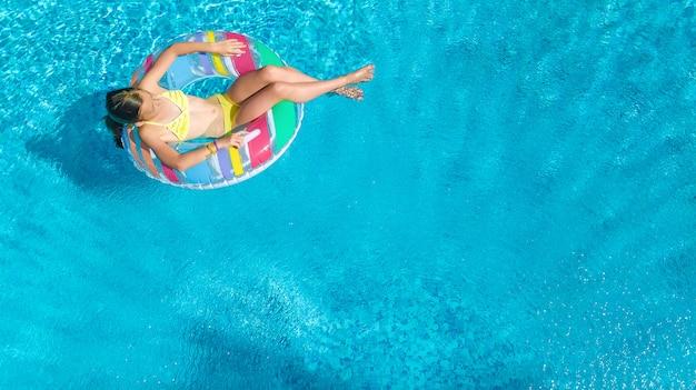 Garota na piscina vista aérea superior de cima, garoto nada na rosca inflável anel, criança se diverte na água azul no resort de férias em família