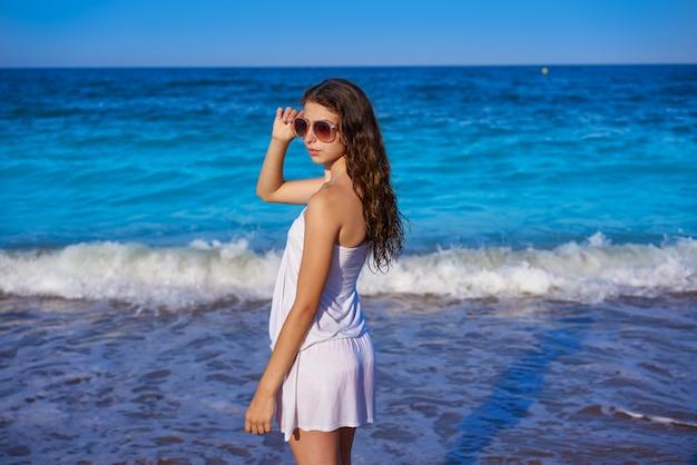 Garota na praia do mar com vestido de verão